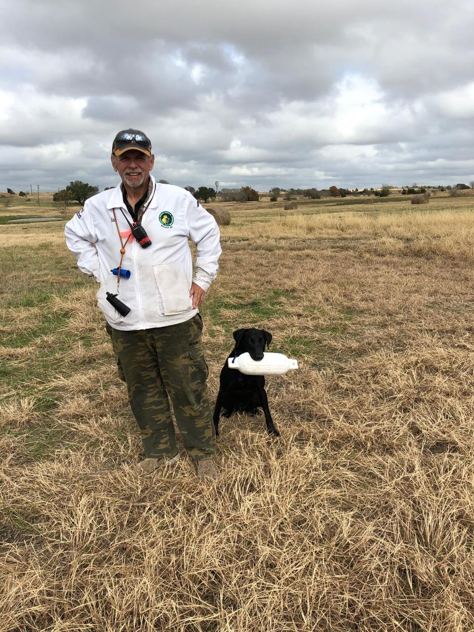 Stu Mead Club Mead Labradors standing in field with Black Labrador Retriever