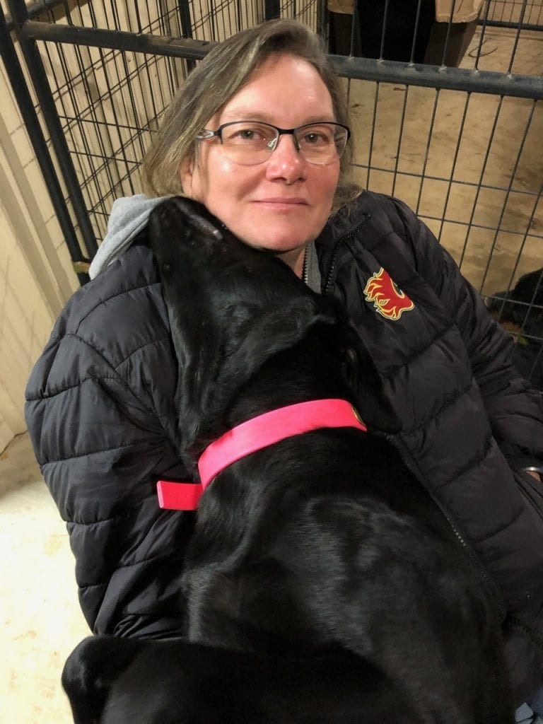 Diana Mead with Club Mead Labrador Retrievers sitting on floor cuddling black labrador