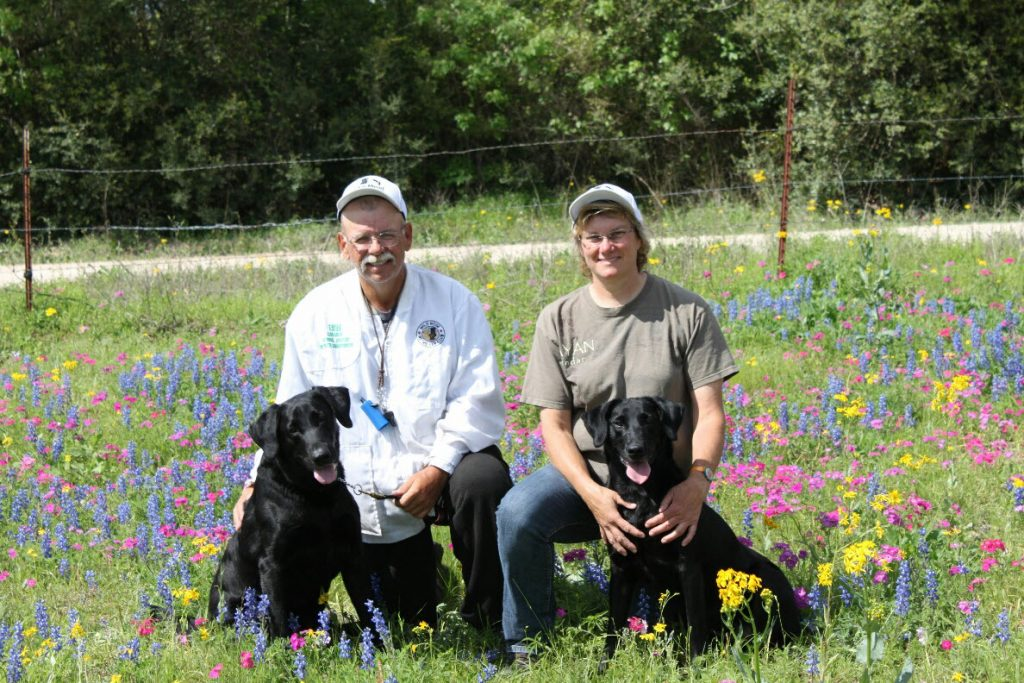 Stu and Diana Mead sitting with black Labrador Retrievers in Meadow with flowers
